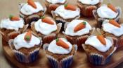 Wortelcupcakes bij elkaar, met witte glazuur en een oranje worteltje erop