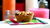 Mini-appeltaartje op een geblokt servetje met kaarsen op de achtergrond