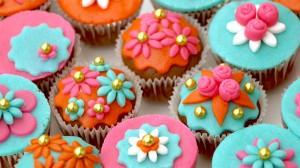Bollywoodcupcakes met oranje, roze en blauwe marsepein en gouden parels