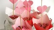 Valentijnsmuffins met frambozen, witte chocola en rode cupcaketoppers in de vorm van een hartje